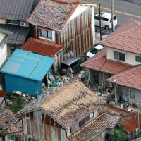 A house is seen with large sections of its roof tiles missing in Kurayoshi, Tottori Prefecture, after the area was hit by a strong earthquake Friday.  | KYODO