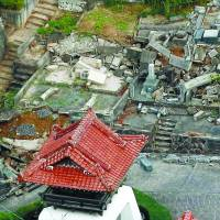 This aerial photo shows broken grave markers and collapsed walls at a cemetery in Kurayoshi, Tottori Prefecture, following a strong earthquake that shook the area Friday. | KYODO