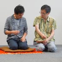Rakugo teacher Tatsuya Sudo instructs a student on how to make use of props when conveying a story to the audience at his English rakugo class in Tokyo last month.   MAGDALENA OSUMI