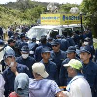 Local residents protest as police try to remove a minivan placed by protesters in the middle of a road near a U.S. military training site in Takae, Okinawa Prefecture, on Sept. 15. | KYODO