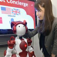 A woman pats Emiew3, a humanoid robot that serves tourists in English, Chinese and Japanese, at JR Tokyo Station, on Monday. | KYODO