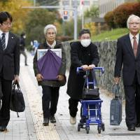 Relatives of a family devastated by a fatal car crash last year enter the Sapporo District Court on Monday. | KYODO