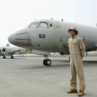 A Self-Defense Forces officer stands guard in front of P-3C patrol aircraft belonging to the Maritime Self-Defense Force in Djibouti in August 2015. | KYODO