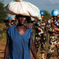 A displaced woman carries goods as United Nations Mission in South Sudan (UNMISS) peacekeepers patrol outside the premises of the U.N. Protection of Civilians site in Juba on Tuesday. | AFP-JIJI