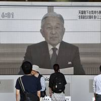 People in Osaka's Umeda district watch a video message Aug. 8 by Emperor Akihito speaking about his feelings on abdication. | KYODO