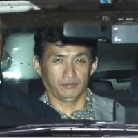 Keitaro Saga, who was arrested Tuesday in connection with the killing of his ex-girlfriend, leaves the Meguro Police Station in Tokyo in a police car Wednesday. | KYODO