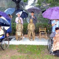 A Korean woman, left, and Chinese woman, right, who say they served as so-called comfort women, attend a ceremony at Shanghai Normal University on Saturday where two statues symbolizing the women who were forced into sexual servitude for Japanese soldiers before and during World War II were unveiled.   KYODO