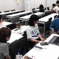 Freelance journalist Laird Harrison, who also serves as director of the Institute for Education in International Media, works with students at the Kindai University during a visit to Kyoto in June. | COURTESY OF RACHELE KANIGEL