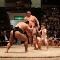 Sumo wrestlers give a demonstration with children from an international school during an event at Tokyo's Ryogoku Kokugikan on Oct. 4. | KYODO