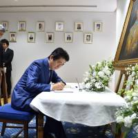Prime Minister Shinzo Abe signs a condolence book for late King Bhumibol Adulyadej at the Thai Embassy in Tokyo on Friday. | AFP-JIJI
