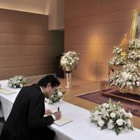 People write their names and messages of condolence in a special book opened at the Thai Embassy in Shinagawa Ward, Tokyo, on Friday following the death of Thai King Bhumibol Adulyadej. | YOSHIAKI MIURA
