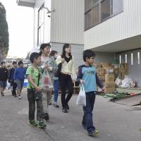 Students on their way to class Monday pass by a school gym that is being used as a quake evacuation center in Kurayoshi, Tottori Prefecture. | KYODO