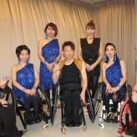 Go Suzuki (center), director of Genesis of Entertainment, a civic group offering activities for disabled and able-bodied people, poses for a photo with fellow members on Oct. 19 after a wheelchair dance performance during the World Forum on Sport and Culture in Kyoto. | KYODO