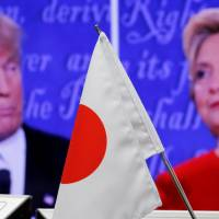 Extremely loud and incredibly close: A Japanese flag stands in front of a monitor showing the first U.S. presidential debate between Republican nominee Donald Trump and his Democratic rival, Hillary Clinton, at a foreign exchange trading company in Tokyo last Tuesday. | REUTERS