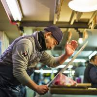 Slice of life: A worker at Tsukiji fish market carves up his catch in a scene from 'Tsukiji Wonderland.' | © 2016 SHOCHIKU