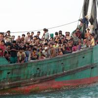 Migrants from Myanmar, including Rohingya Muslims, sit in a boat as they wait to be rescued by Aceh fishermen in the sea off Indonesia in May 2015. | AP