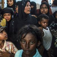 Waiting in vain: Rohingya women and children stand in a shelter in Indonesia's Aceh province after fleeing persecution in Myanmar in May 2015. | AFP-JIJI