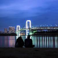 Unconsummated love: A Tokyo couple looks over at the lights of Rainbow Bridge. | ISTOCK