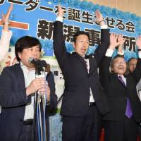 Nuclear foe: Ryuichi Yoneyama (center), a medical doctor who advocates anti-nuclear policies, raises his hands after he was assured of winning the gubernatorial election in Niigata Prefecture on Oct. 16. | KYODO