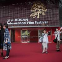 The BIFF fans: Visitors take selfies outside the entrance to the 21st Interational Film Festival, showing their support for the event, which has been beset by controversy over the past two years. | AFP-JIJI