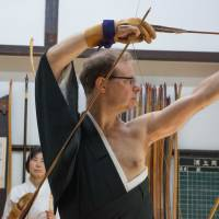 Entering the zone: Jerome Chouchan musters his concentration before firing his first arrow at the Urakami Dojo in Denenchofu, Tokyo. Chouchan wrote the Japanese book 'Target' about the lessons Japanese archery holds for business.   STEPHEN MANSFIELD