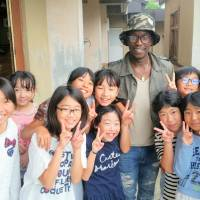 Expanding horizons: Abdou Baye Fall poses with schoolchildren in Fukushima during a visit to the city last month.   COURTESY OF ABDOU BAYE FALL