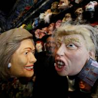 Reality is more frightening: An employee holds up masks depicting U.S. Democratic presidential nominee Hillary Clinton and her Republican rival, Donald Trump, at a shop in Los Angeles on Wednesday. | REUTERS