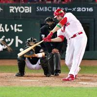 Carp slugger Brad Eldred belts a fourth-inning home run off Fighters starter Shohei Otani in Game 1 of the Japan Series on Saturday. | KYODO