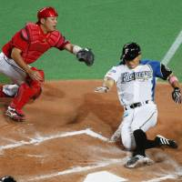 The Fighters' Kensuke Tanaka scores the tying run in the seventh inning. | KYODO