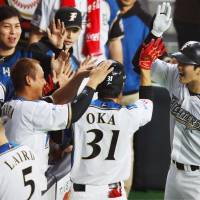 Hiromi Oka is congratulated by teammates after driving in the tying run in the seventh inning on Thursday. | KYODO