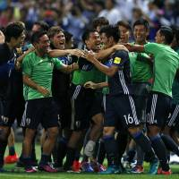 Japan players congratulate Hotaru Yamaguchi (16) after his 95th-minute goal secured a 2-1 World Cup-qualifying win over Iraq at Saitama Stadium on Thursday. | AP