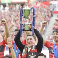 Urawa manager Mihailo Petrovic lifts the J. League Cup winner's trophy on Saturday. | KYODO