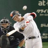 The Giants' Hayato Sakamoto hits a solo home run in the ninth inning on Saturday. | KYODO