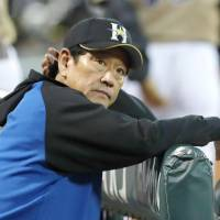 Fighters manager Hideki Kuriyama looks on from the dugout during Hokkaido Nippon Ham's defeat to the Carp in Game 2 of the Japan Series on Sunday.   KYODO
