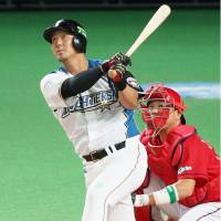The Fighters' Sho Nakata hits a two-run double in the eighth inning on Tuesday. | KYODO