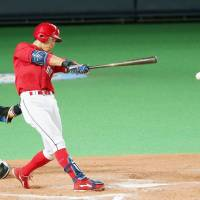 Hiroshima's Tomohiro Abe delivers a game-tying single in the ninth inning. | KYODO