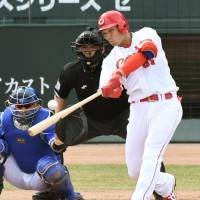 Hiroshima's Seiya Suzuki strokes an RBI single against Yokohama in the first inning of Game 4 of the Climax Series Final Stage on Saturday at Mazda Stadium. | KYODO