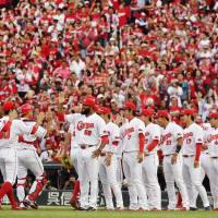 After beating the Yokohama BayStars 8-7 on Saturday, the Hiroshima Carp players congratulate one another for their series-clinching victory in Game 4 of the Central League Climax Series Final Stage at Mazda Stadium. The Carp earned their first trip to the Japan Series since 1991. | KYODO