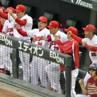 In their dugout, Hiroshima Carp players and staff are fired up about their Central League Climax Series Final Stage-clinching win over the Yokohama BayStars on Saturday afternoon. | KYODO