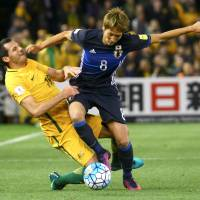 Japan's Genki Haraguchi (right) holds off Australia's Ryan McGowan during their World Cup qualifier in Melbourne, Australia, on Tuesday. | REUTERS