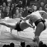 Haguroiwa (left) pushes Taiho out of the ring at the Spring Grand Sumo Tournament in 1969. Haguroiwa, who died Sunday, was declared the winner of the bout but photos and footage later showed that he stepped out of the ring first. | KYODO