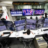 Japanese employees of a foreign exchange trading company work in Tokyo on Wednesday, as U.S. President-elect Donald Trump is seen on television screens delivering his victory speech. | AFP-JIJI