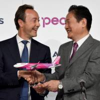 Airbus Chief Operating Officer Fabrice Bregier (left) shakes hands with Peach Aviation CEO Shinichi Inoue at a joint news conference in Tokyo on Friday. | AFP-JIJI