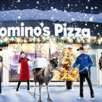 In this image photo uploaded on the official Facebook page of Domino's Pizza Japan, employees of the major pizza chain send out a reindeer with a pizza box strapped around its back to a customer.