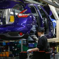 An employee drills into the wheel arch of a Nissan Juke on the production line at the Nissan Motor Co. plant in Sunderland, England, in December 2015. | BLOOMBERG