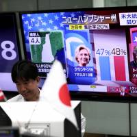 A currency trader observes progress in the U.S. presidential election as a TV channel displays portraits of contenders Hillary Clinton and Donald Trump, at a foreign exchange trading company in Tokyo on Wednesday. | AFP-JIJI