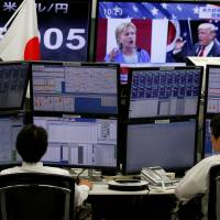 Employees of a foreign exchange trading company work near monitors displaying news about the U.S. | REUTERS