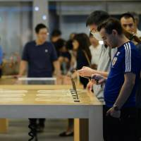 Shoppers try out Apple Inc.'s iPhone 7 smartphones at the company's store in Tokyo's Ginza district on Sept. 27. | BLOOMBERG