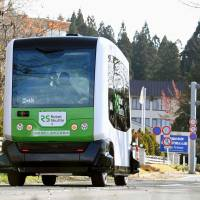 A self-driving bus runs on a public road Sunday in Senboku, Akita Prefecture. | KYODO