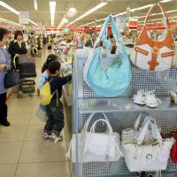 Shoppers browse through clothes in a Shimamura Co. outlet in Saitama Prefecture.   BLOOMBERG